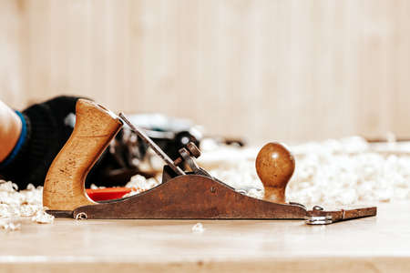 A black jack plane is on a wooden table, next to a wooden sawdust in the workshop Фото со стока