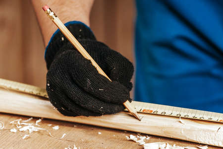 Close-up of a man builder doing the markup on a wooden board with a pencil in a workshop