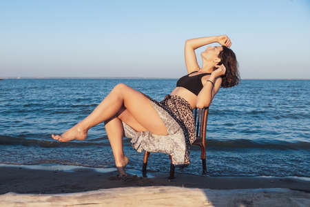 Pretty fresh young woman sitting on chair outdoors in field and wearing in dress in the background a beautiful sea against a blue sky .Concept of summer holidays at village and live style Фото со стока