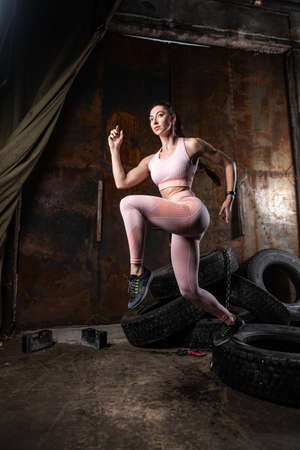 A dark-haired woman coach in a sporty pink short top and gym leggings doing exercise to warm up the legs, alternate knee flexion on a in an old garage, against the background of tires.