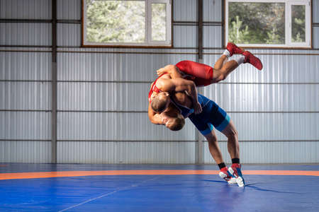 Two men in sports wrestling tights and wrestling during a traditional Greco-Roman wrestling in fight on a wrestling mat. Wrestler throws his opponent's chest through Stockfoto