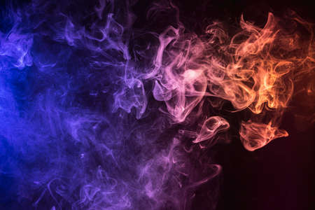 Frozen abstract movement of explosion smoke multiple colors on black background. Background from the smoke of vape