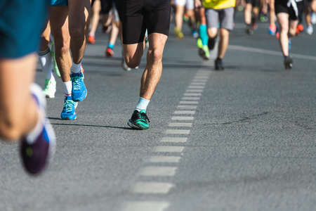 A close-up of the legs of the running track and field athletes on the asphalt. Marathon runners in special sneakers
