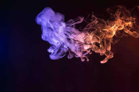 Abstract blue, red and purple smoke on black isolated background. Stop the movement of multicolored smoke on dark background