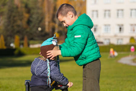 An older brother puts a hat on his little brother in a city park on a warm summer day. Brothers friendship and happy childhood concept. Banque d'images
