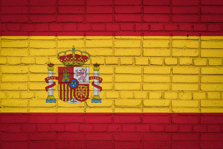 National flag of Spain depicting in paint colors on an old brick wall. Flag banner on brick wall background.