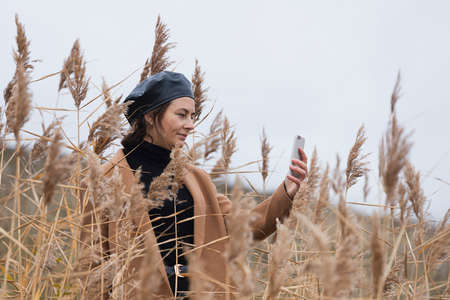 A cheerful dark-haired woman in a black shiny beret and a beige wool coat smiles, takes a selfie enjoy day, on background field in sunny autumn day. The concept of the unity of women and nature, peaceful mood