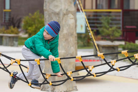 A nimble boy climbs a rope ladder in a hanging city on a playground.