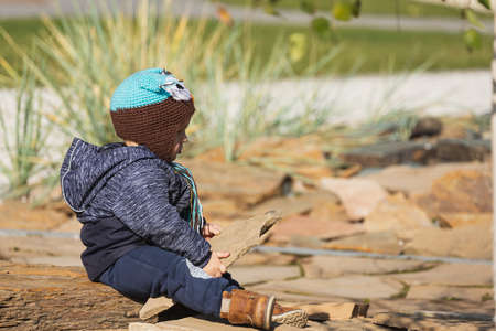 Adorable little 1-2 year old toddler boy having fun and playing with stone on the playground, the child wears a blue jacket with an owl hat