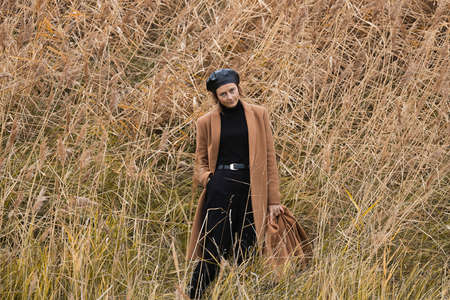 Beautiful romantic woman in a black shiny beret and a beige wool coat on golden field. Concept of autumn holidays at village and live style