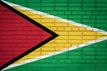 National flag of Guyana depicting in paint colors on an old brick wall. Flag banner on brick wall background.