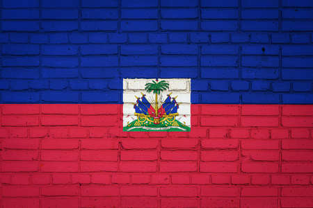 National flag of Haiti depicting in paint colors on an old brick wall. Flag banner on brick wall background.