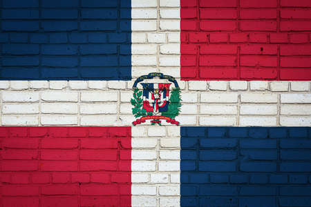 National flag of Dominicana depicting in paint colors on an old brick wall. Flag banner on brick wall background. 免版税图像
