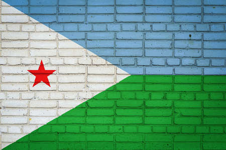 National flag of Djibouti depicting in paint colors on an old brick wall. Flag banner on brick wall background.