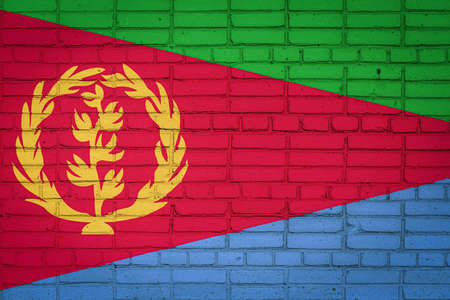 National flag of Eritrea depicting in paint colors on an old brick wall. Flag banner on brick wall background.