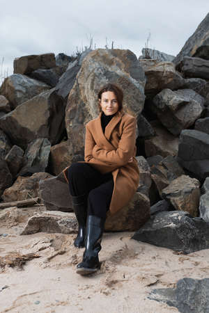 Beautiful romantic woman in a black shiny beret and a beige wool coat on on rocks against sea. Concept of autumn holidays at village and live style