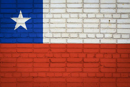 National flag of Chile depicting in paint colors on an old brick wall. Flag banner on brick wall background.