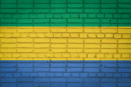 National flag of Gabon depicting in paint colors on an old brick wall. Flag banner on brick wall background. 免版税图像