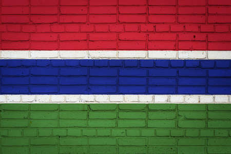 National flag of Gambia depicting in paint colors on an old brick wall. Flag banner on brick wall background.