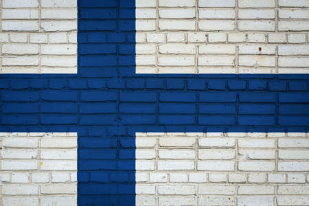 National flag of Finland depicting in paint colors on an old brick wall. Flag banner on brick wall background.