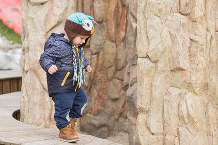 Adorable little 1-2 year old toddler boy having fun on the playground, the child wears a blue jacket with an owl hat