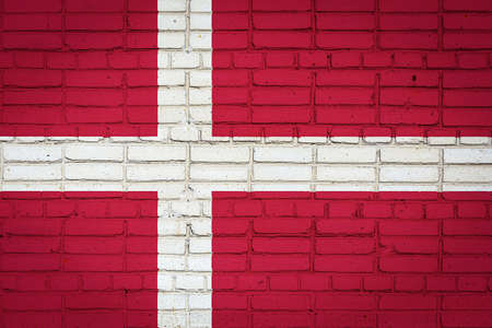 National flag of Denmark depicting in paint colors on an old brick wall. Flag banner on brick wall background.