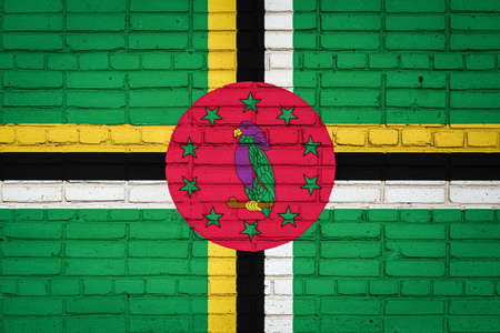 National flag of Dominica depicting in paint colors on an old brick wall. Flag banner on brick wall background.