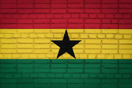 National flag of Ghana depicting in paint colors on an old brick wall. Flag banner on brick wall background.