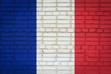 National flag of France depicting in paint colors on an old brick wall. Flag banner on brick wall background.