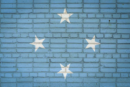 National flag of Federal States of Micronesia depicting in paint colors on an old brick wall. Flag banner on brick wall background.