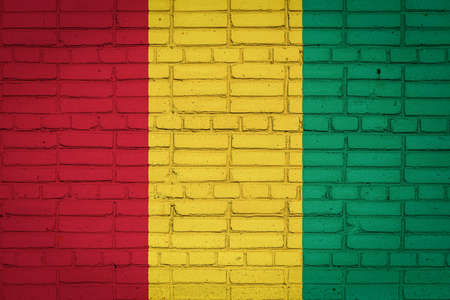 National flag of Guinea depicting in paint colors on an old brick wall. Flag banner on brick wall background.