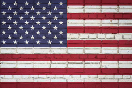 National flag of USA depicting in paint colors on an old brick wall. Flag banner on brick wall background.