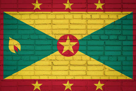 National flag of Grenada depicting in paint colors on an old brick wall. Flag banner on brick wall background.
