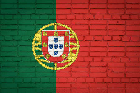 National flag of Portugal depicting in paint colors on an old brick wall. Flag banner on brick wall background.