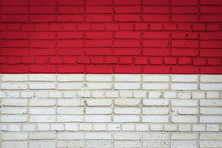 National flag of Indonesia depicting in paint colors on an old brick wall. Flag banner on brick wall background. 免版税图像