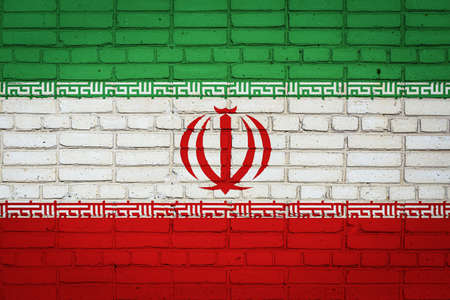 National flag of Iran depicting in paint colors on an old brick wall. Flag banner on brick wall background.