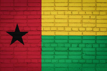 National flag of Guinea Bissau depicting in paint colors on an old brick wall. Flag banner on brick wall background.