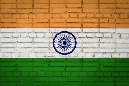 National flag of India depicting in paint colors on an old brick wall. Flag banner on brick wall background.