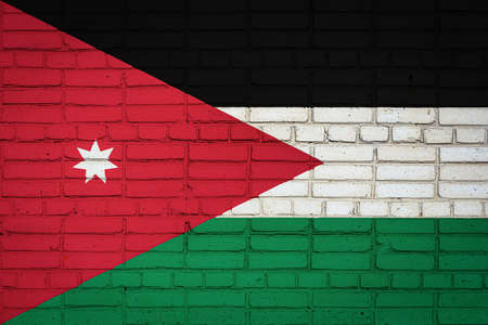 National flag of Jordan depicting in paint colors on an old brick wall. Flag banner on brick wall background.