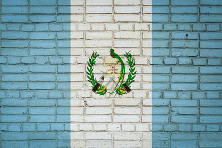 National flag of Guatemala depicting in paint colors on an old brick wall. Flag banner on brick wall background. 免版税图像