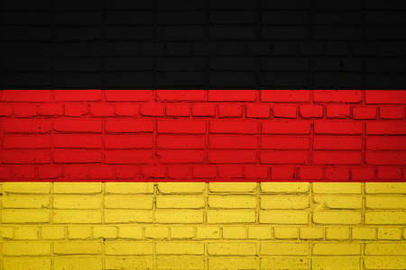 National flag of Germany depicting in paint colors on an old brick wall. Flag banner on brick wall background. 免版税图像