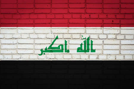 National flag of Irak depicting in paint colors on an old brick wall. Flag banner on brick wall background. 免版税图像