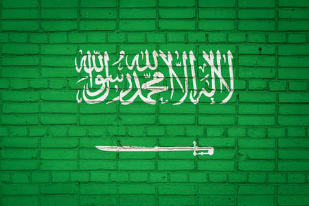 National flag of Saudi Arabia depicting in paint colors on an old brick wall. Flag banner on brick wall background.