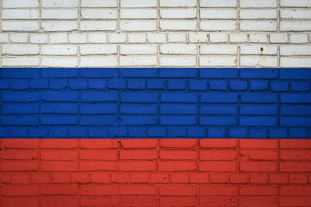 National flag of Russia depicting in paint colors on an old brick wall. Flag banner on brick wall background.