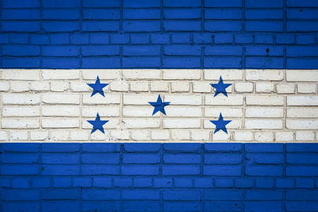 National flag of Honduras depicting in paint colors on an old brick wall. Flag banner on brick wall background. 免版税图像