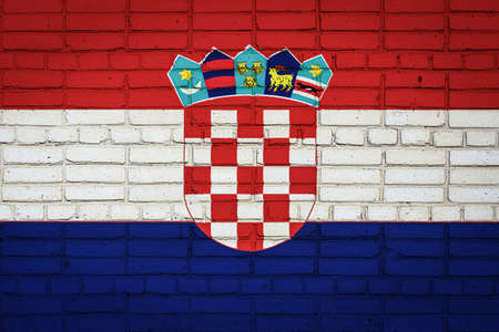 National flag of Croatia depicting in paint colors on an old brick wall. Flag banner on brick wall background.