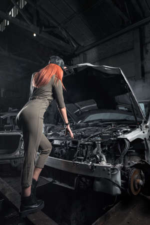 Model in stylish clothes standing against on open hood in disassembled car in the garage. Design Car workshop art concept. Woman repairing an old car in a workshop