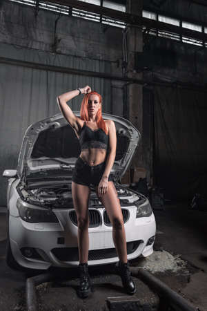 Portrait of a beauty woman in jeans short and top on a background of workshop. Girl model in attractive wear possing with disassembled car in the garage. Banque d'images