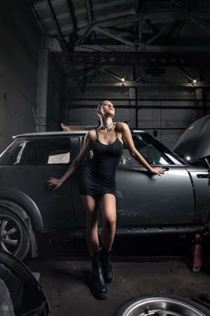 Portrait woman in dress posing next to a car in the garage, in background old car. Creative Colorful Bright Portrait .Design Car workshop art concept Banque d'images - 157861811