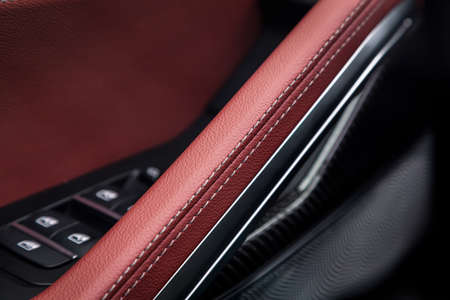 Ð¡lose up of a door control panel with chrome handle on the car door, common black and red genuine leather in a new car. Arm rest in luxury car